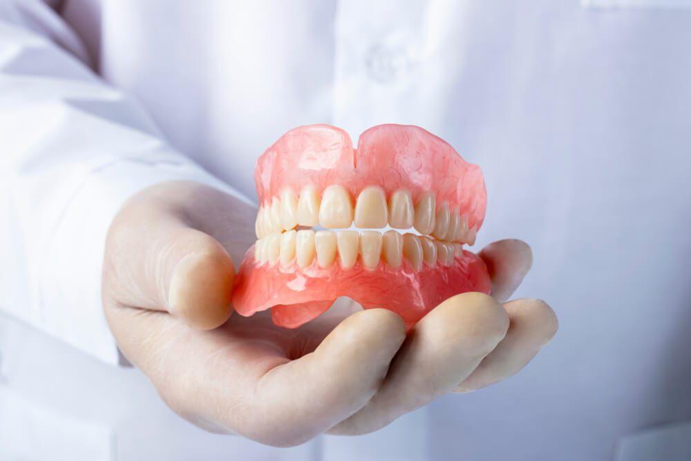 dentist holding dentures