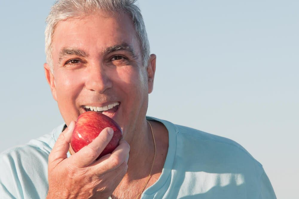 male eating apple with dentures