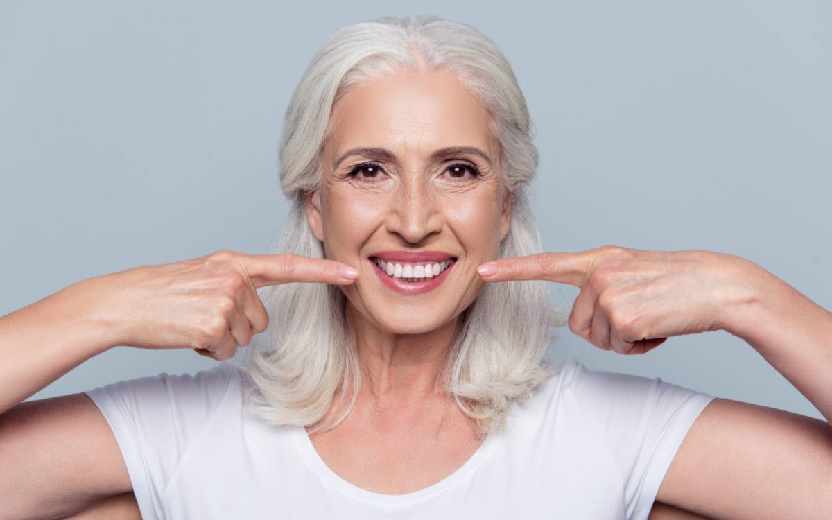 Smiling woman pointing at new dental implants